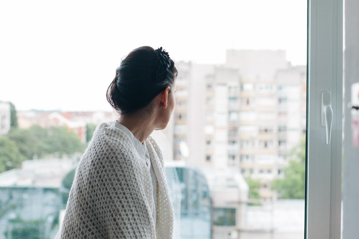 Woman looking outside in front of her window